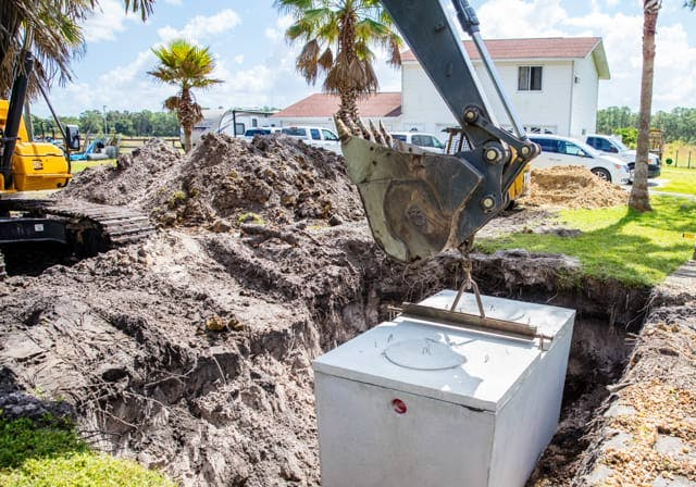 Excavator lowering a septic system