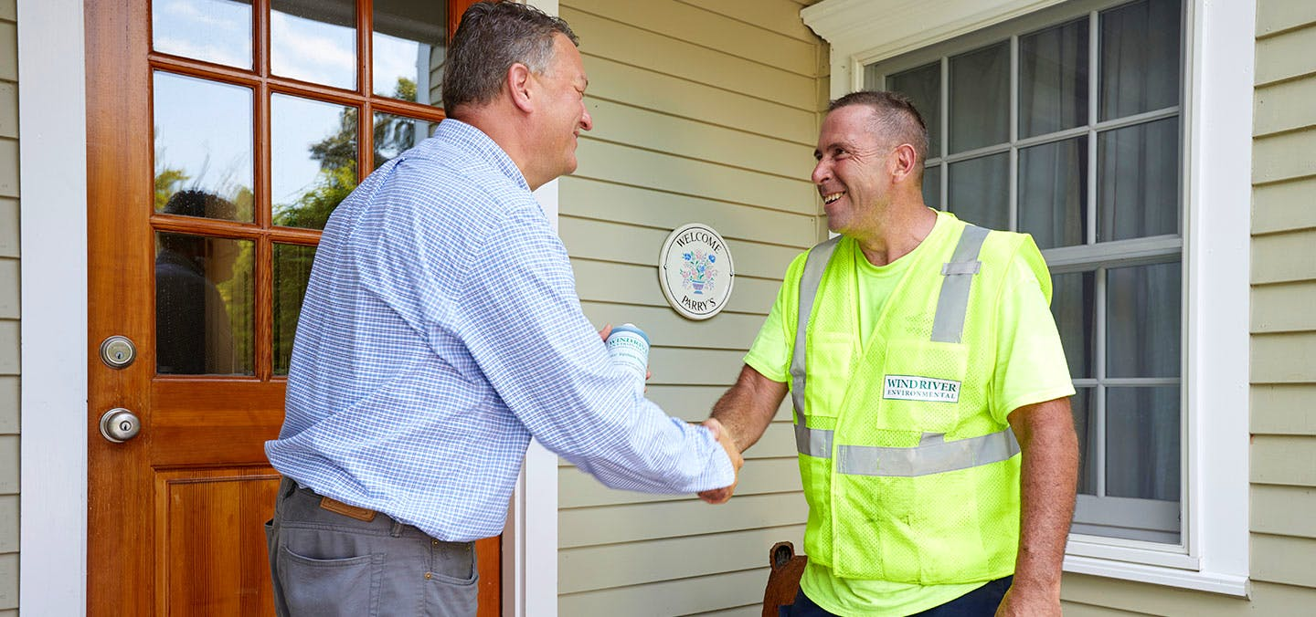 A Wind River Environmental employee shaking hands with a homeowner